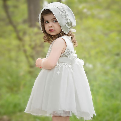 A toddler wears a knee-length white dress with a bonnet.