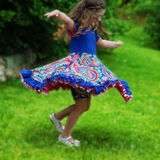 a little girl spinning in a colorful dress