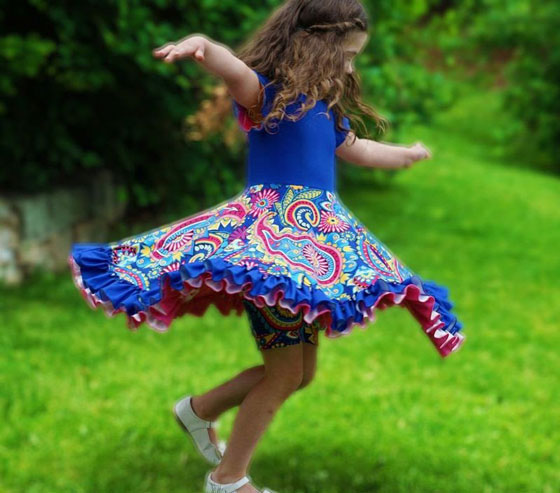 a little girl wearing a twirling rainbow dress