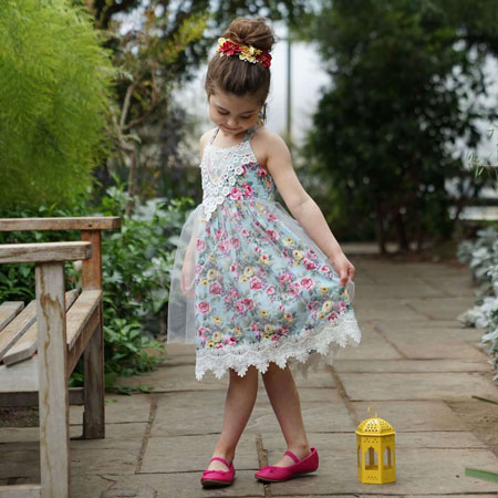 A little girl wears a blue floral dress and red shoes