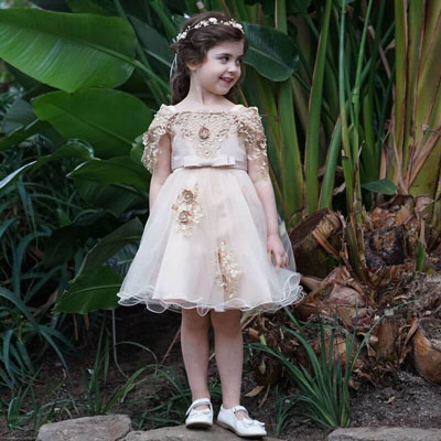 A little girl wears a knee-length caramel dress with a flower tiara and white shoes.