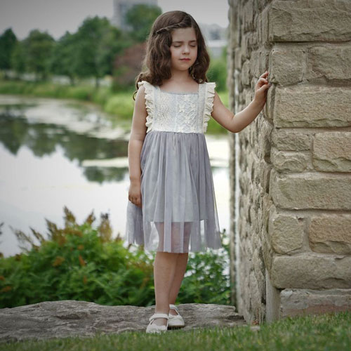 little girl in a grey and cream dress