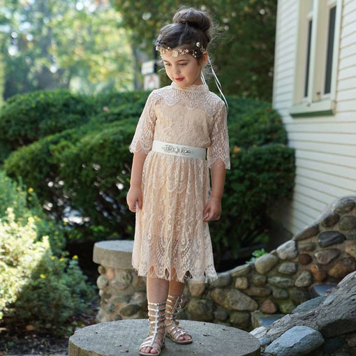 A little girl wears a long white lace dress