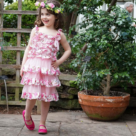 A little girl wears a pink multilayer dress and a pink crown