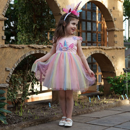 A little girl wears a rainbow unicorn dress and a unicorn headband