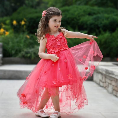 A young girl wears a red dress with a multilayer tulle skirt.