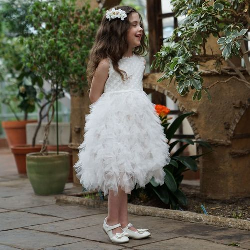 a little girl in a white ruffled dress