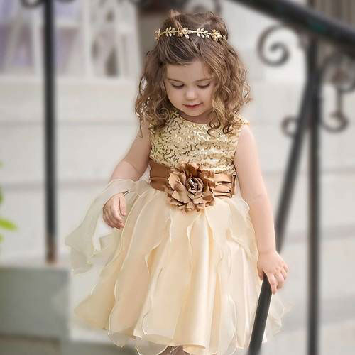 A young girl wears a gold sequin dress