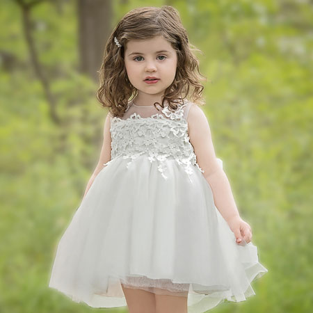A little girl wears a short white dress and a bonnet