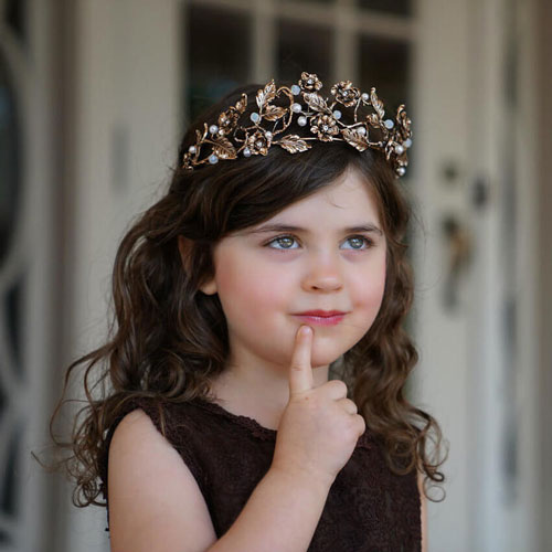 A young girl wearing a tiara touches her chin with her index finger